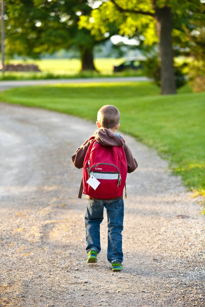 boy in brown hoodie carrying red backpack while walking on dirt road near tall trees